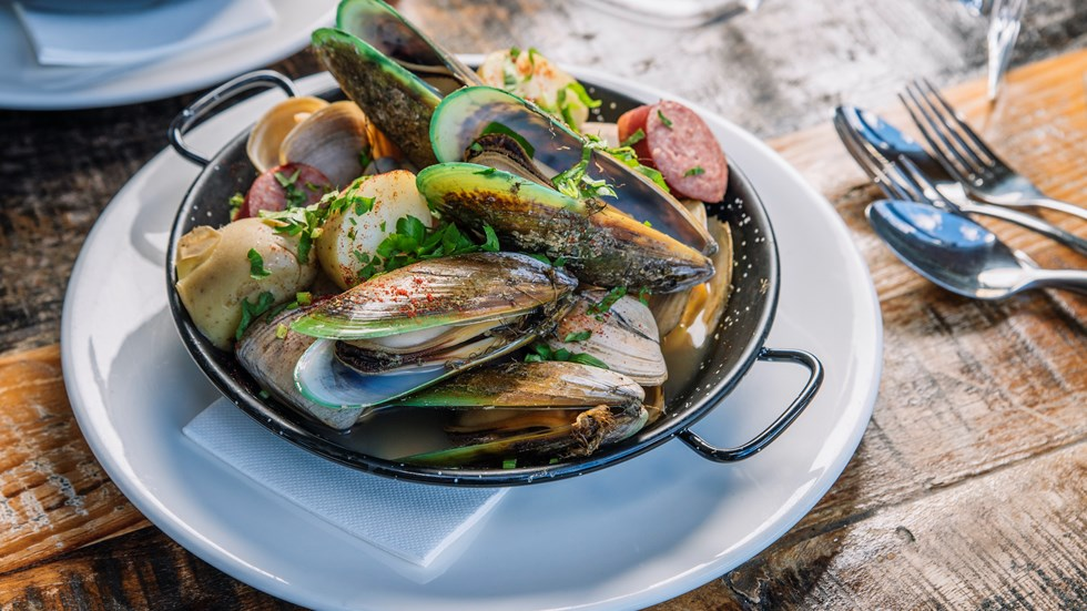 A plate of fresh local Greenshell mussels and clams served at Furneaux Lodge on the Queen Charlotte Track in the Marlborough Sounds, New Zealand.