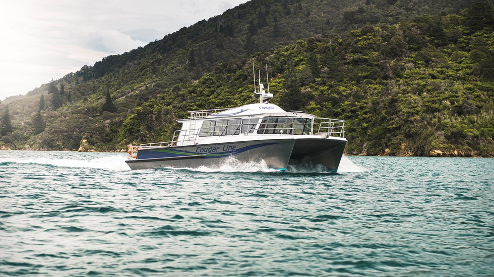 The name on the side of Cougar Line's Sounds Exciting boat sits above the boat's wake, while cruising the Marlborough Sounds, New Zealand