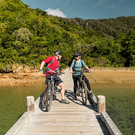 A couple on mountain bikes on the jetty at Ship Cove/Meretoto, Marlborough Sounds, New Zealand.