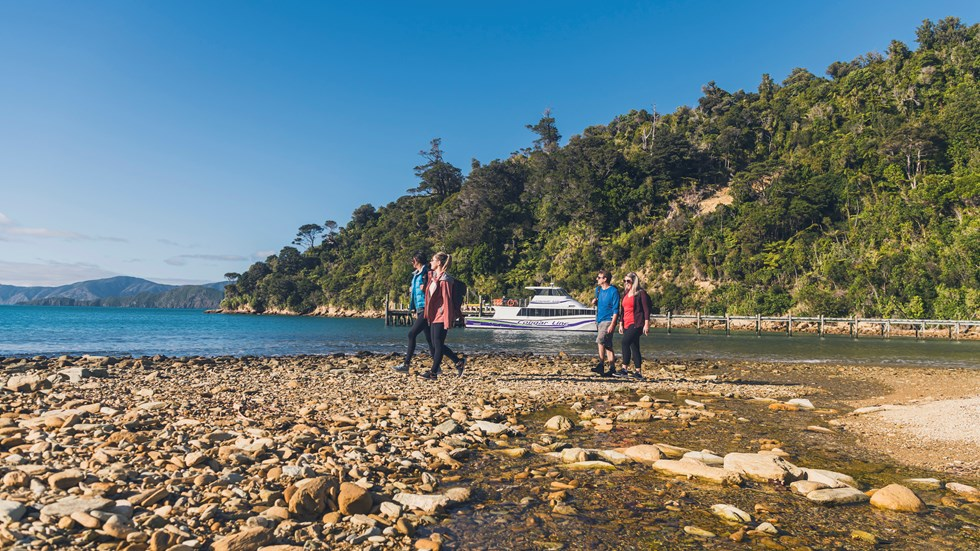 Four people walking on the beach at Ship Cove/Meretoto with a Cougar Line boat in the Marlborough Sounds, New Zealand.