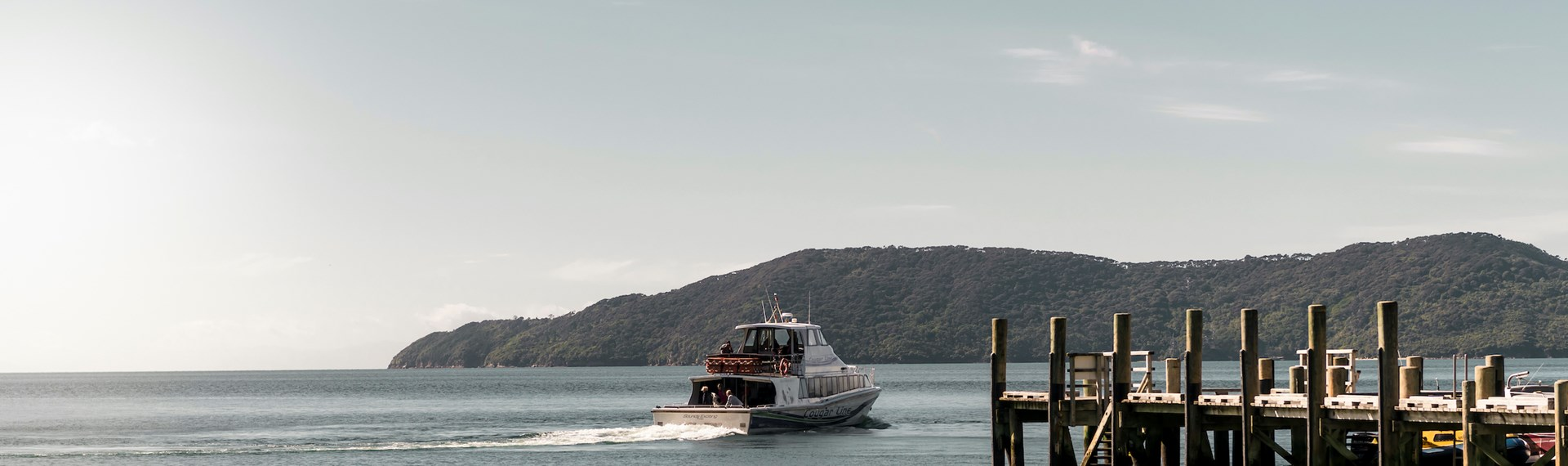 A Cougar Line boat departs the jetty at Ship Cove/Meretoto in the outer Queen Charlotte Sound/Tōtaranui in the Marlborough Sounds, New Zealand.