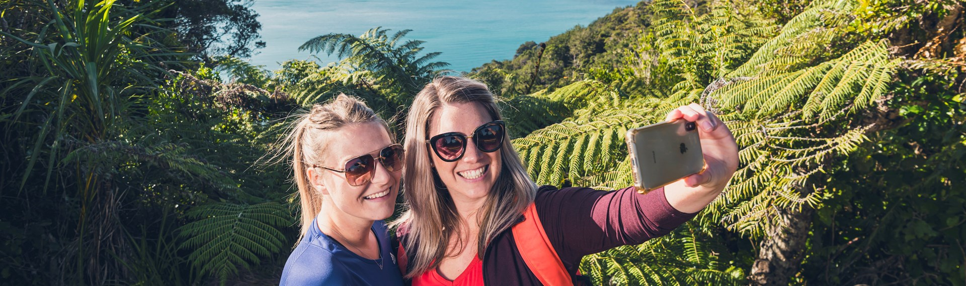 Two women take a selfie at a viewpoint on the northern Queen Charlotte Track in the Marlborough Sounds, New Zealand.