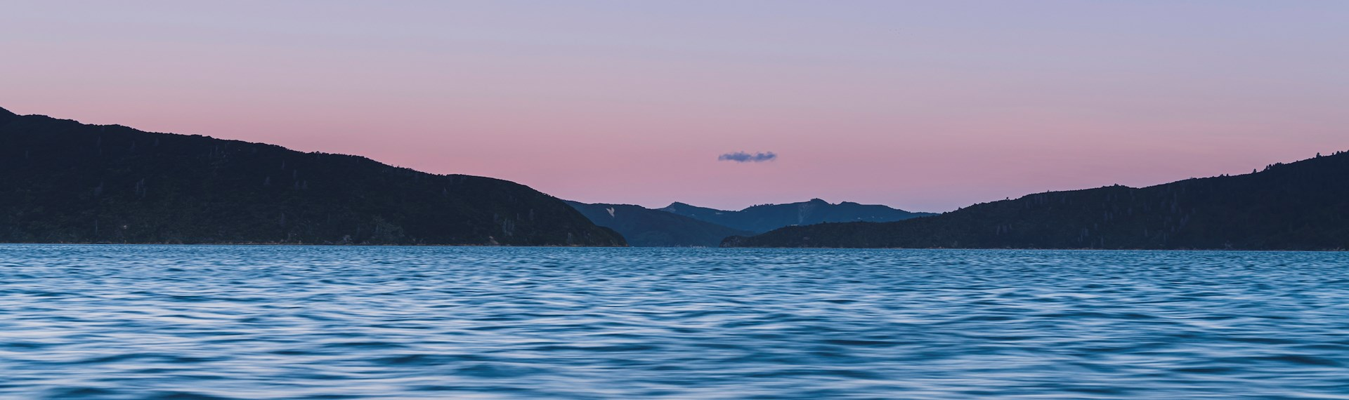 The Marlborough Sounds water, hills and full moon at sunset, Marlborough, New Zealand.