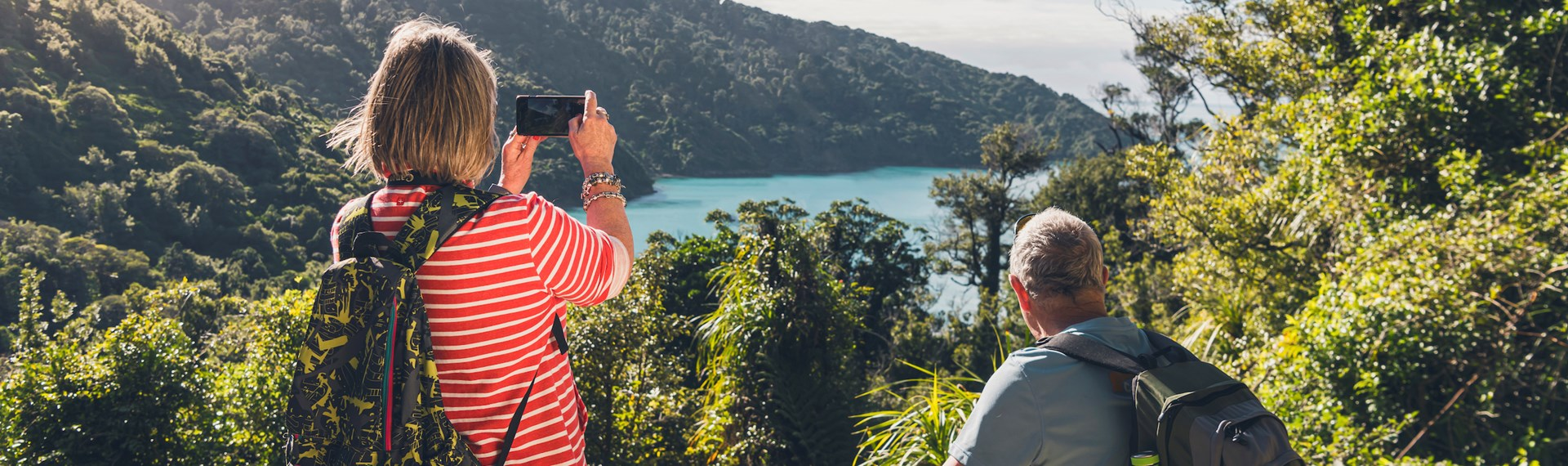 A woman takes a photo on her phone of the view across Ship Cove/Meretoto while a man sits on a bench on the northern Queen Charlotte Track in the Marlborough Sounds, New Zealand.