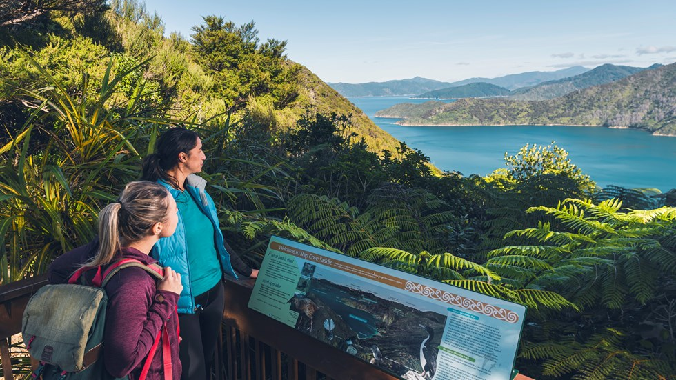Two women admire the view over Ship Cove/Meretoto and read an interpretive sign in the outer Queen Charlotte Sound/Tōtaranui, Marlborough Sounds, New Zealand.