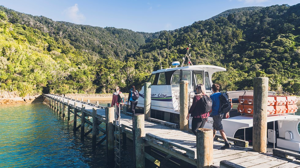 Four people walk on the jetty at Ship Cove/Meretoto next to a Cougar Line boat in the Marlborough Sounds, New Zealand.