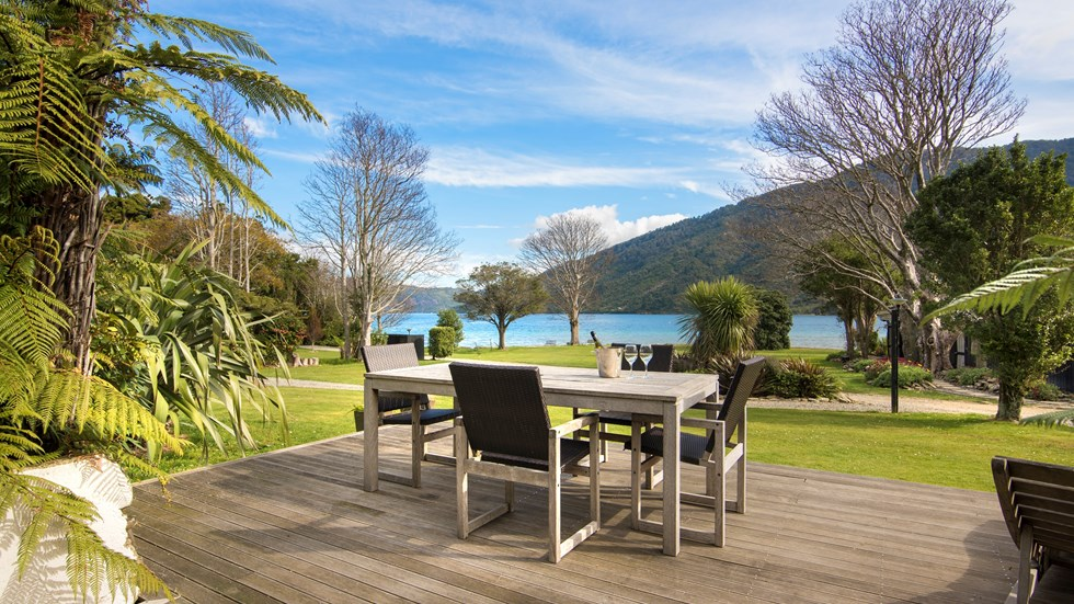 The view from a Cook's Cottage at Furneaux Lodge overlooks the furnished outdoor deck, sweeping green lawn and Endeavour Inlet in the Marlborough Sounds, New Zealand
