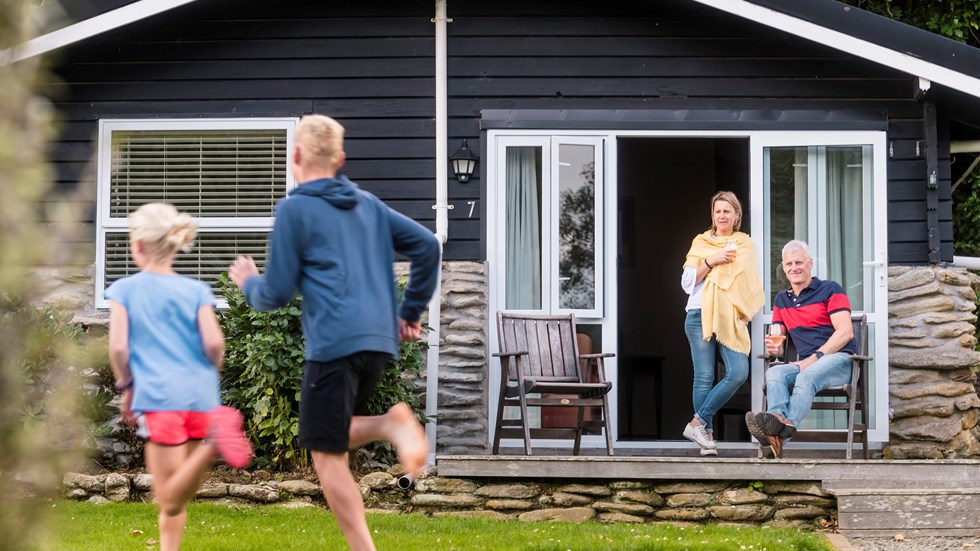 Two children run on the lawn of Furneaux Lodge while their parents enjoy a glass of wine on the deck of their Cook's Cottage in the Marlborough Sounds, New Zealand