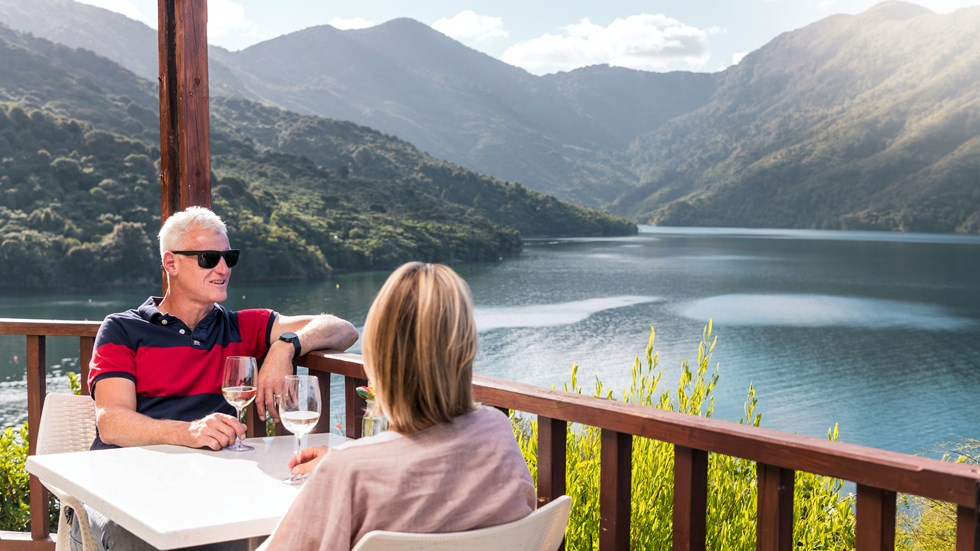 A couple sit at a table on the deck of the Punga Cove restaurant with wine, admiring the view of Endeavour Inlet in the Marlborough Sounds, New Zealand.