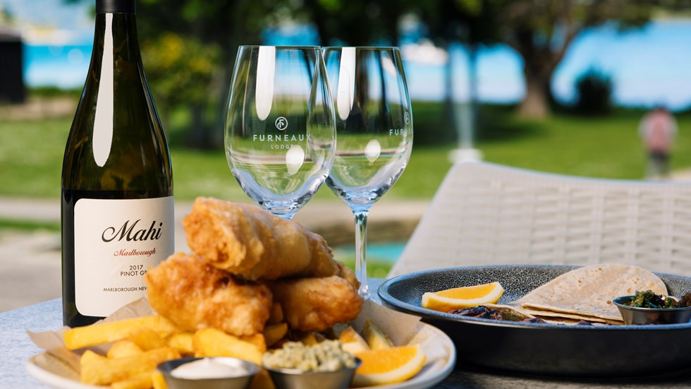 A plate of fish and chips and wine served at Furneaux Lodge in the Marlborough Sounds, New Zealand.