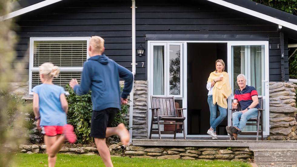 Two children run on the lawn of Furneaux Lodge while their parents watch from a Cook's Cottage with a glass of wine in the Marlborough Sounds, New Zealand.