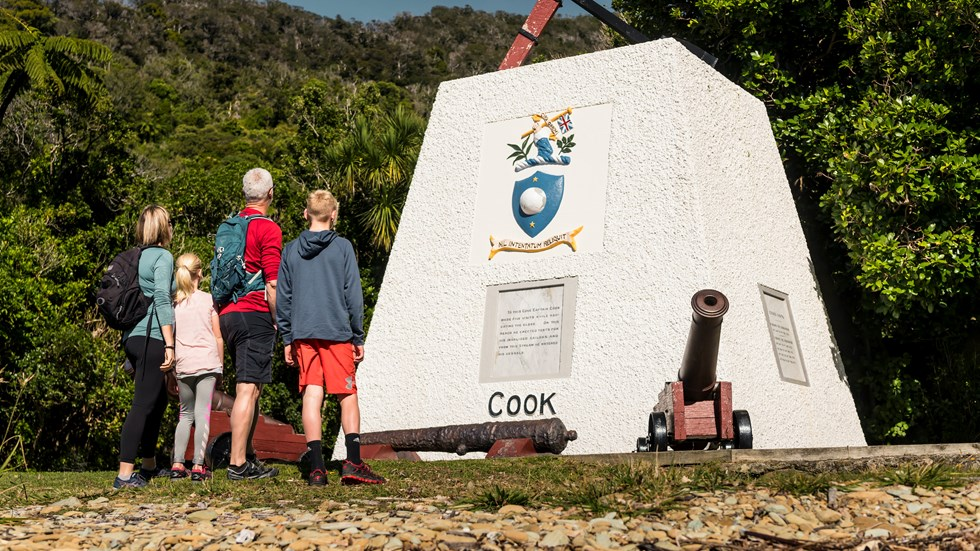 Four people look at the monument to Captain James Cook at Ship Cove/Meretoto in the Marlborough Sounds, New Zealand.