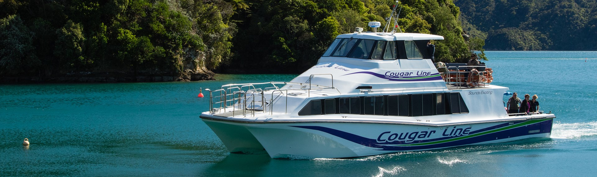 A Cougar Line boat with passengers onboard cruises into a calm bay in the Queen Charlotte Sound/Tōtaranui, Marlborough Sounds, New Zealand.