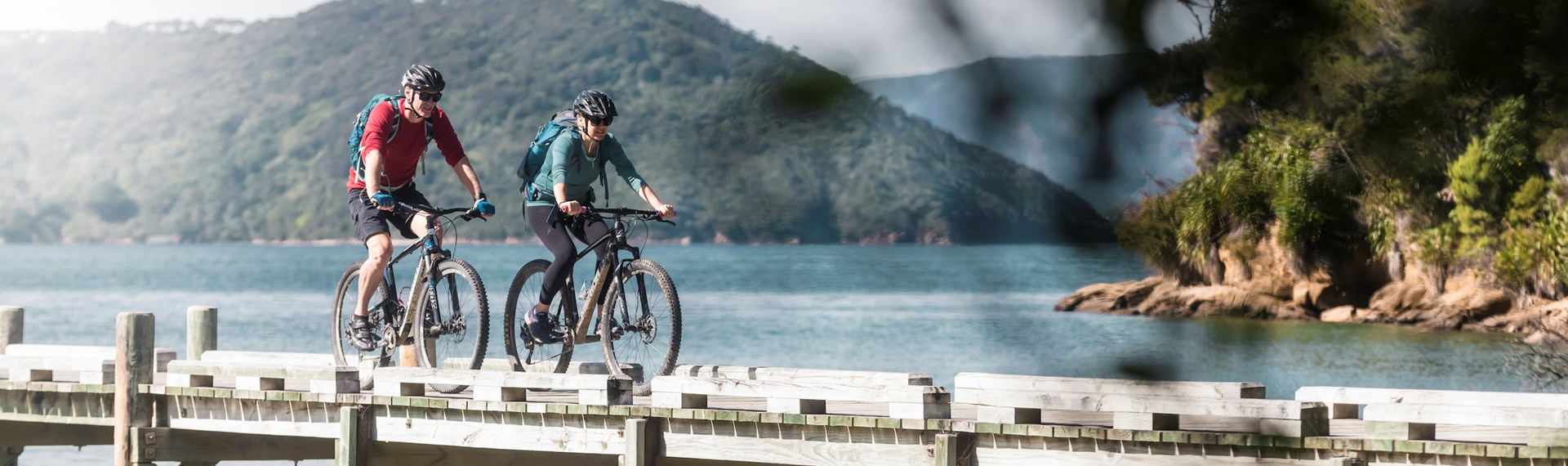 Two mountain bikers on the jetty at Ship Cove/Meretoto, about to start the Queen Charlotte Track in the Marlborough Sounds, New Zealand.