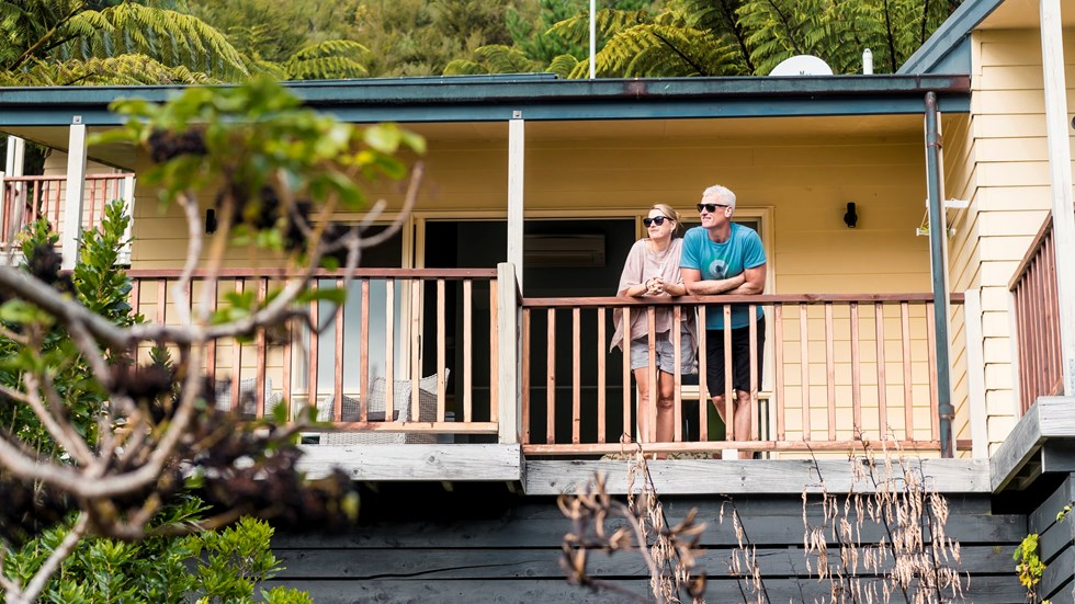 A couple stand on their room's private sun deck at Punga Cove to admire the sea view of the Marlborough Sounds, New Zealand.