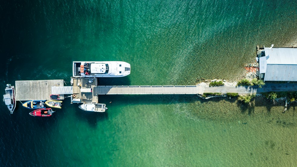 An aerial view of the Furneaux Lodge jetty, boat shed, Cougar Line boat and smaller boats in the Marlborough Sounds, New Zealand.