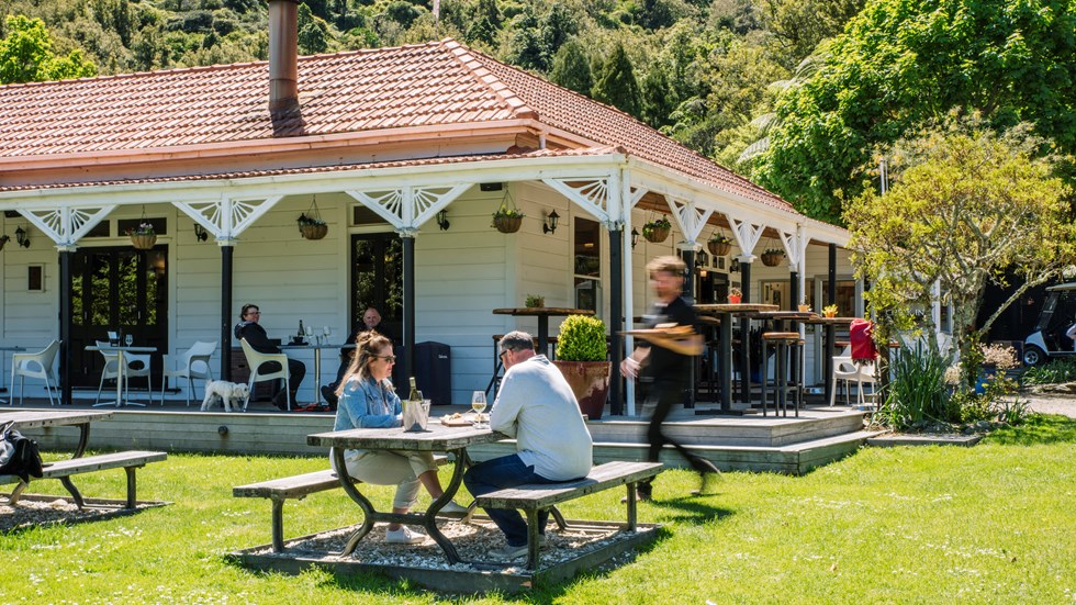 Two people are served by a waiter on the lawn while dining at Furneaux Lodge in the Marlborough Sounds, New Zealand.