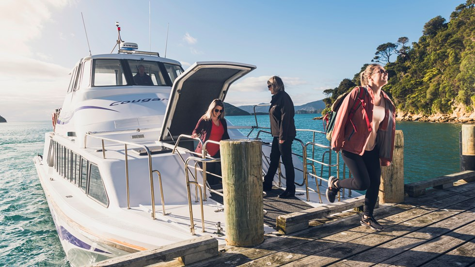 Cougar Line passengers disembark the boat at Ship Cove/Meretoto to start the Queen Charlotte Track in the Marlborough Sounds, New Zealand.